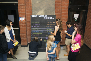 """Katy Galaz, second from right, hosts a group of attendees at the """"Interactive Chalkboard Intervention."""" (Photo: Mallory Shibe)"""