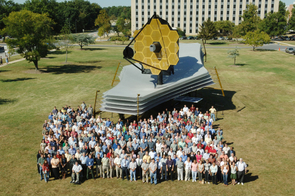 Members of the JWST team at Goddard Space Flight Center give a sense of scale to a mock-up of what will be the largest space telescope ever built. (Photo: NASA)