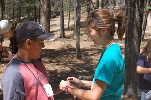 Jen Dang, a UA psychology major, ties bracelets on a camper's wrist.(Photo courtesy of Kristen Petersen)