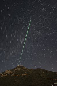 (Click to enlarge) A bundle of laser beams creates five artificial stars in the night sky above Mount Hopkins in Southern Arizona. Laser light reflected by air molecules is analyzed by a computer that drives the actuators on the adaptive mirror. (Image courtesy of Thomas Stalcup)