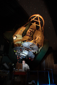 (Click image to enlarge) Robert McMillan observing with an experimental instrument unrelated to his asteroid work in 2007, in the dome of the Steward Observatory's 2.3-meter Bok Telescope on Kitt Peak. (Photo: Dave Harvey/Steward Observatory)