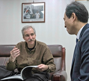 Kim Newton (left) meets Opposition Democracy Party floorlLeader Woo Sang-ho, who has the 1987 photo taken by Newton hanging in his office. In the image, Woo holds a picture of slain student Lee Han-yeol. (Photo courtesy of Kim Newton)