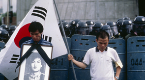 The two Woos, former student activists, were photographed by Newton in 1987, with Sang-ho holding the photo of Lee during a memorial procession. Lee was killed during a student uprising. (Photo: Kim Newton)