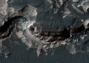 This is a more detailed close-up view of the HiRISE image of Holden crater. It shows layers revealed when Holden crater rim was breached, unleashing water that scoured out parts of Holden crater. From the bottom up, these include the base of impac megabreccia, contrasting smooth sedimentary layers, another darker, crudely layered unit, and dark wind-blown material on the surface. These layers correspond to layers in the illustrative drawing, above left.