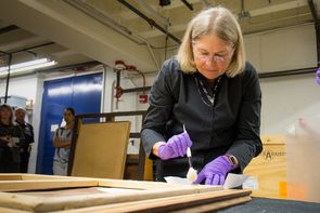 "Nancy Odegaard uses a brush to remove dust from ""Woman-Ochre."" Odegaard is a world-renowned conservator who works at the Arizona State Museum on the UA campus. (Photo: Bob Demers/UANews)"