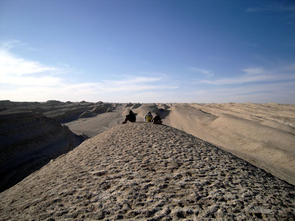 Researchers sit atop a wind-formed ridge called a yardang located in the Qaidam Basin of Central Asia. The yardangs in that area can be as much as