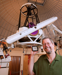 Richard Kowalski of the UA-operated Catalina Sky Survey holds a piece of 2008 TC3, the first-ever meteorite discovered while still cruising through space.  (Credit: Full Moon Photography)