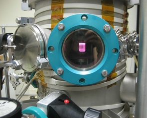 (Click to enlarge) A window into Titan's atmosphere: Energized by microwaves, the gas mix inside the reaction chamber lights up like a pink neon sign. Thousands of complex organic molecules accumulated on the bottom of the chamber during this experiment. (Photo: S. Hörst)