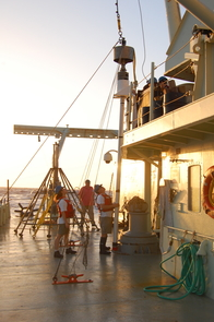 Scientists on a research cruise prepare a sediment corer for deployment. The approximately 20-foot coring device will be lifted by a crane over the side of the ship and lowered to a depth of more than two miles, at which point the device will penetrate the seafloor and recover a sediment core. The length of the core would represent about 40,000 years of time. (Photo: Peter deMenocal)