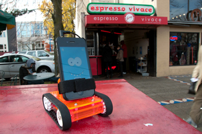 Romo, the smartphone-controlled robot, allows its human controller to see, talk to and interact with others without leaving home. It also can run errands. Here, Romo pauses outside a Seattle coffee shop. (Photo courtesy of Peter Seid and Phu Nguyen)