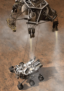 Mars rover Curiosity is lowered to the ground by a skycrane.