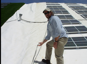 (Click to enlarge) Nate Allen, sustainability coordinator at Biosphere 2, explains a demonstration site at Biosphere 2 showing how solar panels can be effectively mounted on steep slopes like mine tailings.