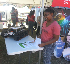 Ty'Dria Wright White, treasurer of the UA chapter of NSBE, explains features of a robotic rover to homecoming visitors. (Photo: Daniel Stolte/UANews)
