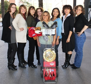 The College of Public Health UA Cares Team includes, from left to right, Katie Sprague, Donna Knight, Griselda Martinez, Alayna Voutsas, Mary Contreras, Sonia Romero, Rebecca Ruiz and Jackie Leon. Pictured with them is the one-of-a-kind trophy designed by Tucson artist Ned Schaper.