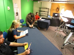 "Students involved with the ""Dorm Room Sports Chat"" program prepare before the show. Part of the student-led station's mission is to involve UA students in professional broadcasts with other experience in management, sales and production. (Photo courtesy of UATV)"