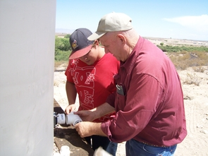 UA student Tyler Pearce, of Safford, works with Graham County Cooperative Extension Director Bill Brandau to install rainwater harvesting tanks at Discovery Park in Safford, a facility owned and managed by Eastern Arizona College.