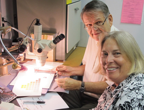 Wayne Wesolowski and Nancy Odegaard examining paint flakes. (Credit: Arizona State Museum)