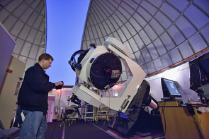 Adam Block adjusts the telescope to point to an object in the evening sky. (Photo: David Harvey)