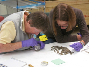Researchers Frances F. Berdan and UA alumna Alyson M. Thibodeau examine loose samples of adhesive and turquoise mosaic tiles associated with a collection of Mixteca-style turquoise mosaics at the Smithsonian Institution-National Museum of the American Indian. (Photo courtesy of Frances F. Berdan)