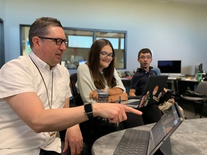 "Rob Wisner, director of digital innovation at the Arizona Daily Star, works with Erin Thomson and Phillip Bramwell on their mobile app, ""Tucson Access Guide."" (Photo: Michael McKisson)"