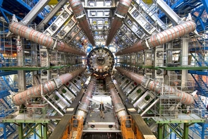 A person stands in front of the huge ATLAS detector, one of six detectors that are part of the Large Hadron Collider near Geneva.