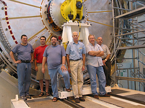 UA physicist John Rutherfoord (center, in the light blue shirt) and colleagues are dwarfed by part of the forward calorimeter, the device the team developed and built for ATLAS. Pictured, from left, are Alexandre Savine of the UA; Phillipe Gravelle from Carleton University in Ottawa; Peter Loch of the UA; Rutherfoord; Leif Shaver of the UA; Mircea Cadabeschi from the University of Toronto.
