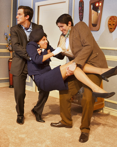 "Bernard (Parker Janecek) and Robert (Michael Calvoni) attempt to forcibly remove Italian stewardess, Gabriella (Carli Naff), from Bernard's apartment in order to keep the other fiancée stewardesses from finding out about her in the UA Arizona Repertory Theatre's production of ""Boeing Boeing."" (Photo credit: Ed Flores)"