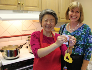 Professor Supapan Seraphin, left, takes a break from making curry to show her Ben's Bell, and Jennifer Horner, who nominated Seraphin for the award.