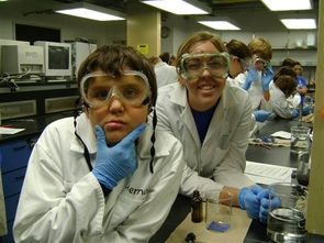 Camper and mentor participating in a science experiment.