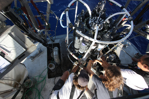 Scientists aboard the Tara Oceans vessel prepare to lower a CTD device into the blue depths. A suite of sampling containers and instruments allows them to collect specimens and data at the same time. (Photo: Anna Deniaud/Tara Oceans)