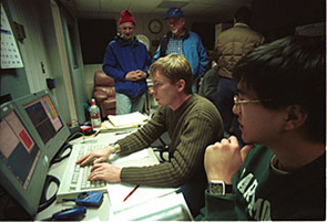 Philip Hinz (center), joined by Wilson Liu (lower right) and William Hoffmann (upper left) on an observing run earlier this year at the 6.5-meter MMT telescope in Arizona. They used the 6.5-meter Magellan telescope in Chile in discovering a dust disk around a young star. The dust disk has a gap, believed to result from a forming planet. (Photo: Lori Stiles)