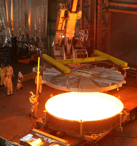 """Casting of a 4 meter mirror substrate made of """"Zerodur"""" glass ceramic on June 2, 2006 at SCHOTT headquarters in Mainz, Germany. The molten glass is heated to more than 2,732 degrees Fahrenheit (1,500 degrees Celsius). After cooling and preliminary processing, the substrate is ceramized in an 11-month process in which the glass is transformed to glass ceramic. (Image: SCHOTT)"""