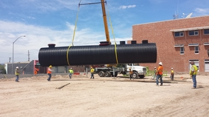 Construction workers with one of three sections of a 52,000-gallon underground water harvesting tank at the ENR2 building. (Photo courtesy of UA Planning, Design & Construction)