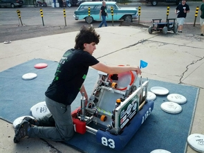 "A member of Tucson community robotics team Bit Buckets loads Frisbees into a robotic Frisbee launcher at ""Maketopolis."" (Photo courtesy of Maketopolis)"