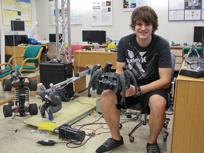 Matt Bunting in the UA Robotics and Neural Systems Lab, holding the hexapod robot that has created a huge buzz among robotics fans. A protoype of Bunting's latest project, robotic cheetah legs, can be seen lower left.