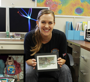 """How it all began: Veronica Bray shows a photo of herself when she was 6, holding her """"favorite birthday present"""" – a book about the universe (see inset at lower left). (Photo: Shipherd Reed/UA)"""
