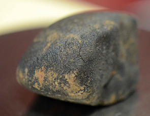 Its edges rounded during its violent entry into Earth's atmosphere, this meteorite was splattered with dirt upon impact. (Photo: Patrick McArdle/UANews)