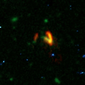 A composite image showing ALMA data (red) of the two galaxies of SPT0311-58. These galaxies are shown over a background from the Hubble Space Telescope (blue and green). The ALMA data show the two galaxies' dusty glow. The image of the galaxy on the right is distorted by gravitational lensing. The nearer foreground lensing galaxy is the green object between the two galaxies imaged by ALMA. (Credit: ALMA (ESO/NAOJ/NRAO), Marrone, et al.; B. Saxton (NRAO/AUI/NSF); NASA/ESA Hubble)