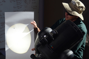 Projecting the Sun's image with the small dot of Venus onto a piece of paper, SkyCenter Director Alan Strauss re-creates the first historic recording of a Venus transit made in 1639. (Photo: Patrick McArdle/UANews)