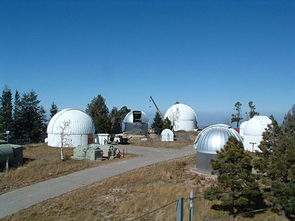 Overview of Steward Observatory's Mount Lemmon Observatory. The 24-inch SkyCenter telescope used for  public evening observations is at left. The silver-colored dome will house the Catalina Sky Survey's refurbished 40-inch telescope by summer. The white dome at center is the 60-inch Catalina Sky Survey telescope.