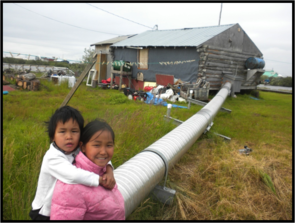 Children in the village of Selawik, Alaska play on an insulated water line. Because of thawing permafrost, lines are sinking, causing junctions to stress, break, and then in the winter, freeze. (Photo: Mike Brubaker, Alaska Native Tribal Health)