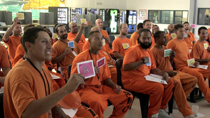 Incarcerated students vote on questions using colored cards. (Photo: Arlene Islas/University Communications)