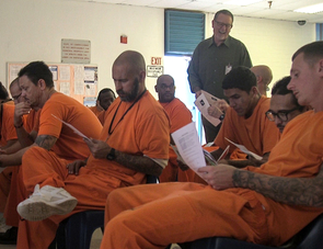 Incarcerated students work in groups to complete a worksheet that checks their understanding while astronomy professor Ed Prather answers questions. (Photo: Arlene Islas/University Communications)