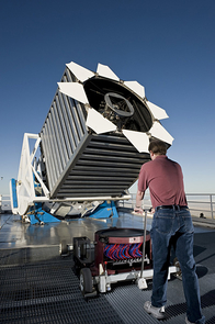 "Engineer Dan Long loads the first cartridge of the night into the Sloan Digital Sky Survey telescope. The cartridge holds ""plug-plates"" at the top, which then hold a thousand optical fibers shown in red and blue. The cartridges are locked into the base of the telescope and changed many times overnight."