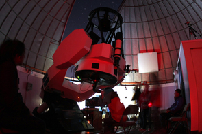 Bundled up against the chilly air on top of Mt. Lemmon, students use the Schulman Telescope for a night of observing planets, stars and galaxies. (Photo: Adam Block)