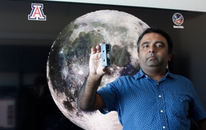 Jekan Thanga holds a FemtoSat developed in the UArizona SpaceTREx Laboratory. (Photo: Emily Dieckman/College of Engineering)