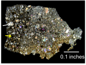 """A thin section of the meteorite from this study seen in cross-polarized light. """"Viewing it that way can help identify different minerals in the thin section – but it's also prettiest that way,"""" Miller said. """"The dark section on the left is the primitive clast we've been studying. The white arrow is pointing to a large silicate chondrule, and the yellow arrow is pointing to a sulfide chondrule, which is black in this view."""" (Photo courtesy of Kelly Miller)"""