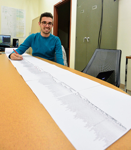 Bioinformatics undergraduate student Thomas Kidder working with a printout of the 1KP green plant phylogeny. The scroll of paper outlining the gene families of the plant tree of life measures about 50 feet. (Photo: Mike Barker)