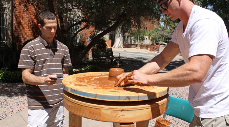 Art student Steve Carcello crafts a pot on a replica of an ancient Greek pottery wheel as biology student Dan Pont measures the wheel's speed. (Photo by Beatriz Verdugo/UANews)