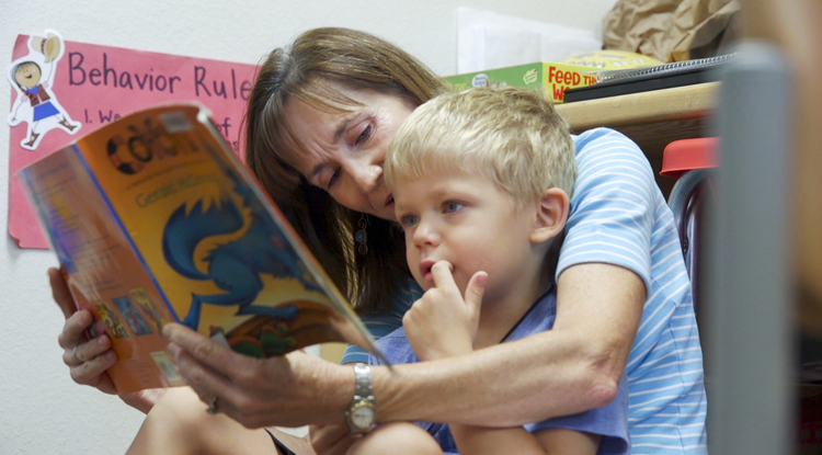 Speech pathologist Rebecca Vance reads to a boy as part of an annual summer camp conducted by the UA's Department of Speech, Language and Hearing Sciences. (Photo: Bob Demers/UANews)
